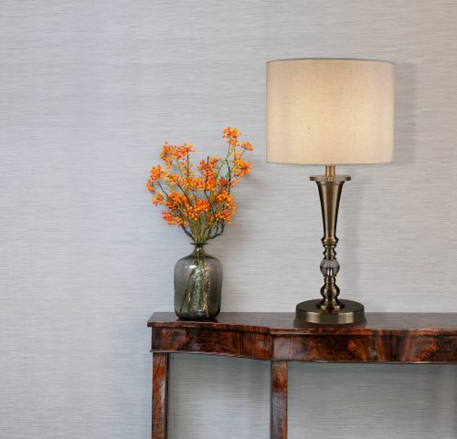 1011-searchlight-sobremesa-comprar-electricidad-aranda-almeria-clasica-moderna-bronde-pantalla-Sideboard in front of a grey wall with flower vase